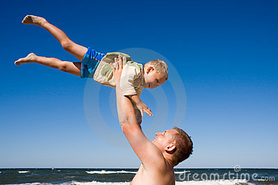Father play with son on beach