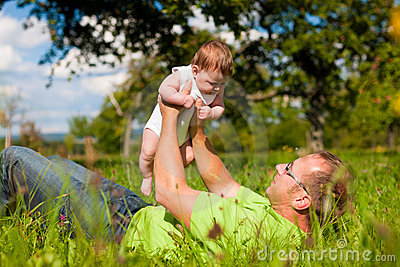Father playing with baby on meadow
