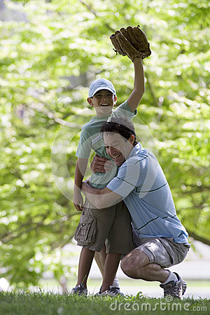 Father playing with son (10-12) in park, boy wearing baseball glove, hand raised, smiling, portrait Stock Photo