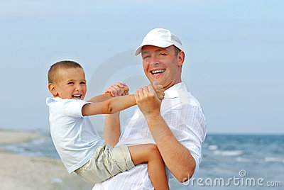 Father playing with young son on the beach