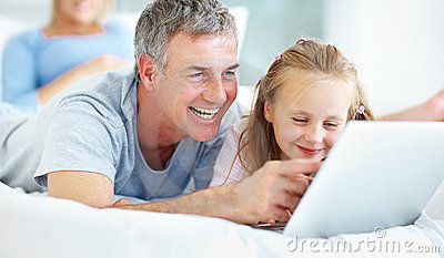 Father pointing at laptop screen with his daughter