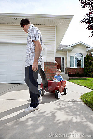 Father Pulling Son Sitting in Wagon