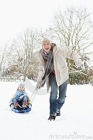 Father Pulling Son On Sledge Through Snow