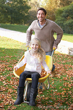 Father pushing child through autumn leaves