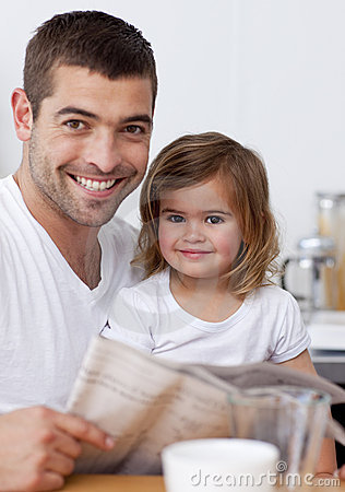 Father reading a newspaper with his daughter