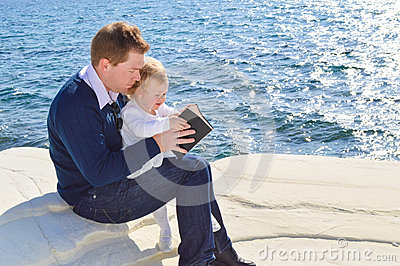 Father reading the Bible to his daughter