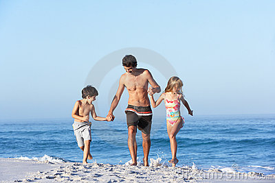 Father Running With Children Along Sandy Beach