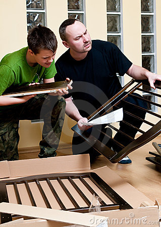 Father and son assemble crib