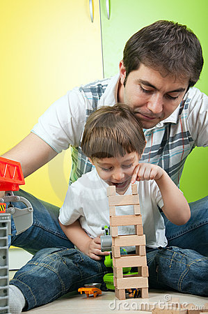 Father and son building a wooden toy tower