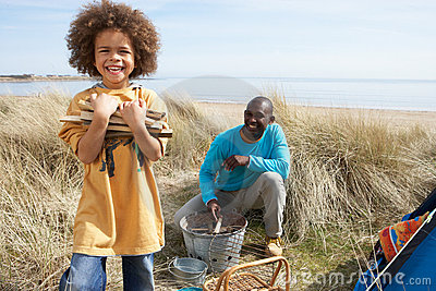 Father And Son Collecting Firewood On Beach
