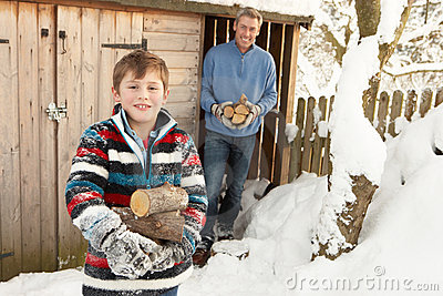 Father And Son Collecting Logs From Wooden Store