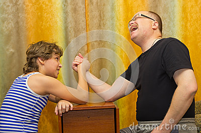 Father and son compete in arm wrestling