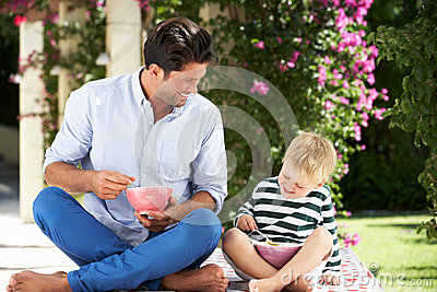 Father And Son Enjoying Breakfast Cereal Outdoors