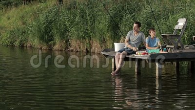 Father and son enjoying fishing together on lake stock video footage