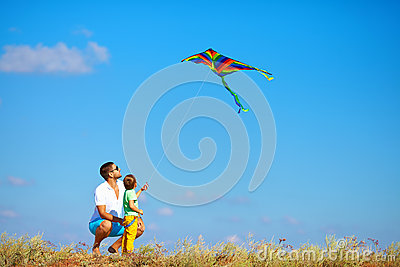 Father and son having fun, playing with kite