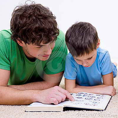 Father and son indoors reading book