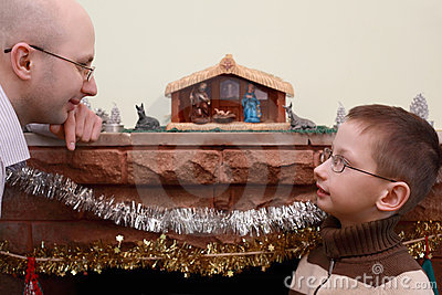 Father and son look at each other near fireplace