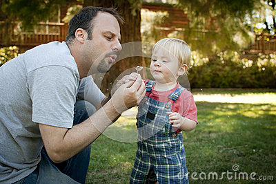 Father and son at the park blowing on dandelion
