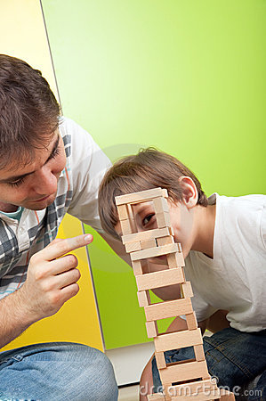 Father and son playing with construction toy set