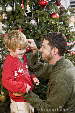 Father and son playing in front of Christmas tree