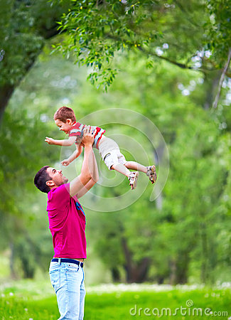 father and son playing outdoors in spring forest