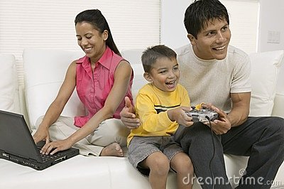 Father and son playing video game, mother using pc