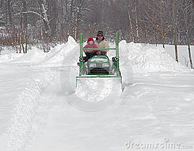 Father and son plow a snowy drive on a tractor