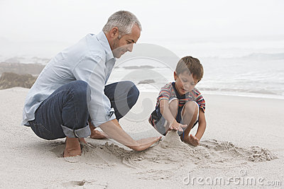 Father And Son Preparing Sand Castle