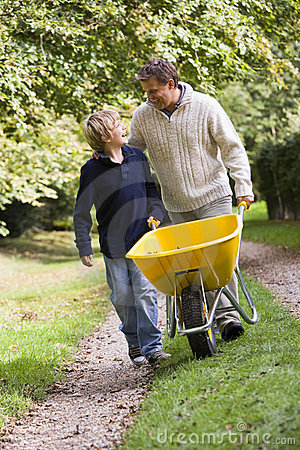 Father and son pushing wheelbarrow