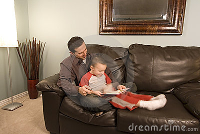 Father and Son Reading a Book on the Couch