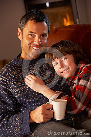 Father And Son Relaxing With Hot Drink Watching TV