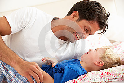Father And Son Relaxing Together In Bed