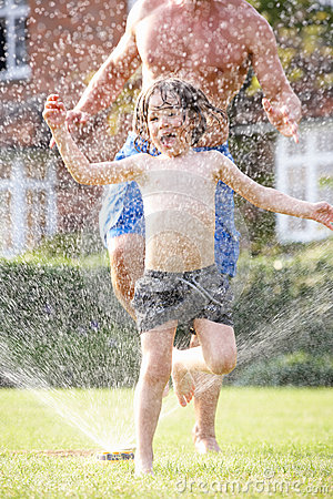 Father And Son Running Through Garden Sprinkler