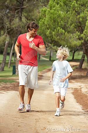 Father and son running in park