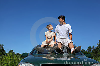 Father and son sit on roof of car in day