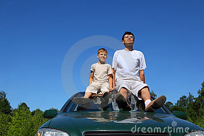 Father with son sit on roof of car in day-time