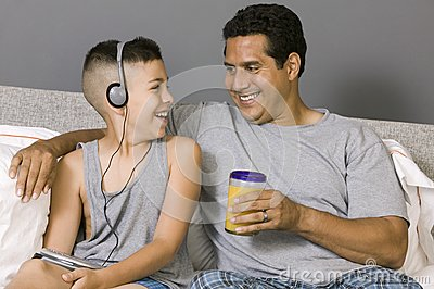 Father and Son sitting on bed Listening to Music