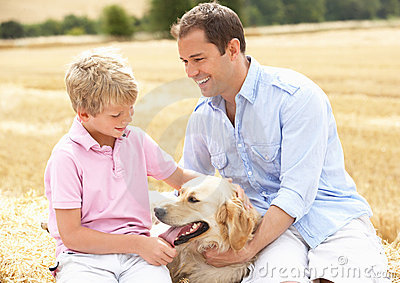 Father And Son Sitting With Dog On Straw Bales In