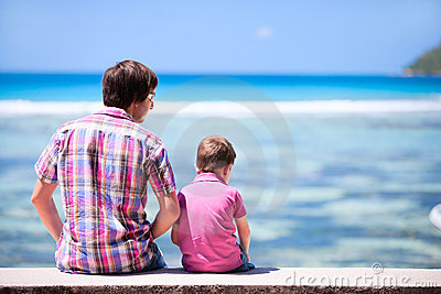 Father and son sitting by the ocean