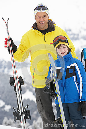 Father And Son On Ski Holiday In Mountains