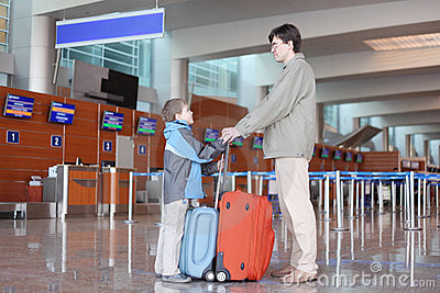 Father and son standing in airport hall