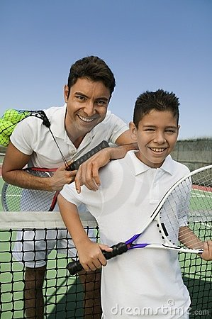 Father and son standing t on tennis court