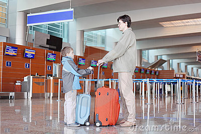 Father and son with suitcase in airport hall