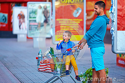 Father and son with trolley after shopping