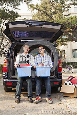 Father and son unpacking car for college, holding bins and looking at camera