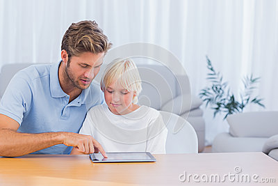 Father and son using tablet pc together