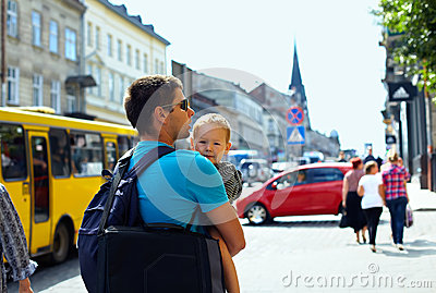 Father, son walking through crowded city street
