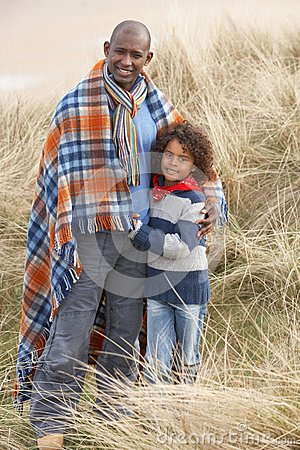 Father And Son Wrapped In Blanket Amongst Dunes On