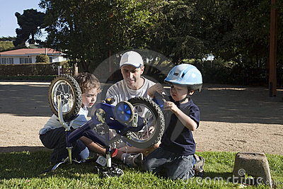 Father and sons fixing bike