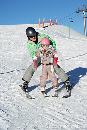 Father Teaching Daughter To Ski Whilst On Holiday